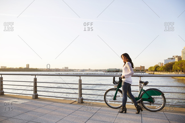 Side View Of Woman Walking With A Bike On Promenade Against Clear