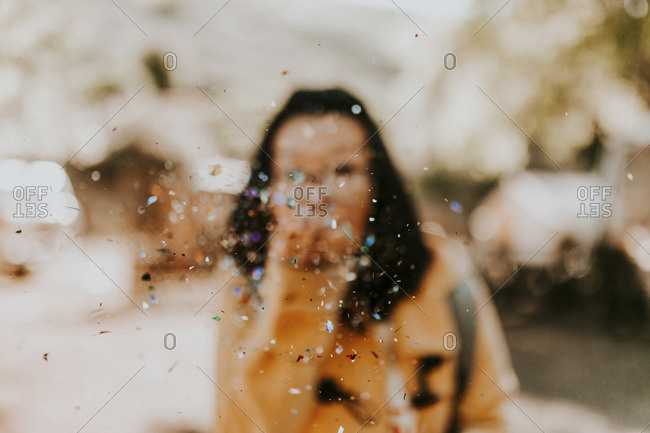 Woman spraying confetti on street