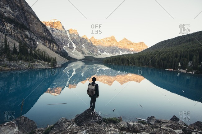 Rear view of male hiker standing by calm lake and mountains during winter