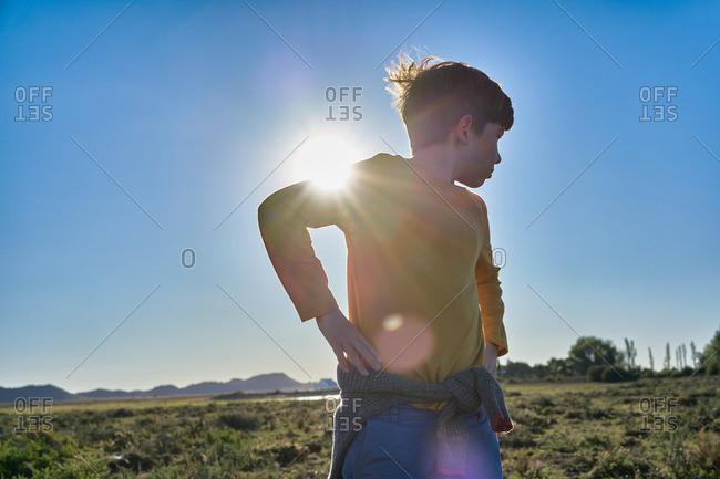 Boy standing in a vast desert plain