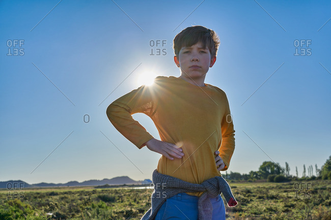 Boy standing on a desert plain with his hand on his hips
