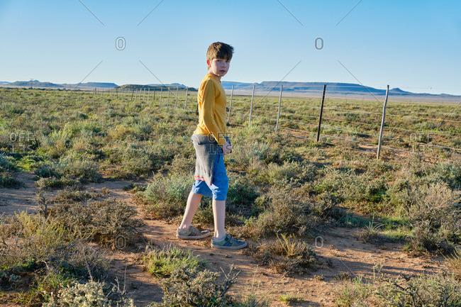 Boy standing near a fence in a desert scrubland