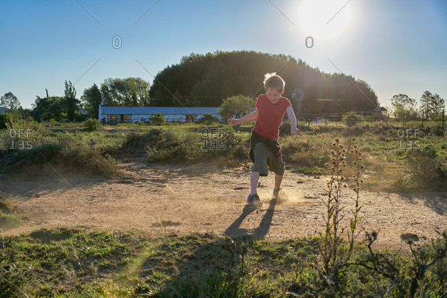 Boy playing on a dirt patch in a desert scrubland