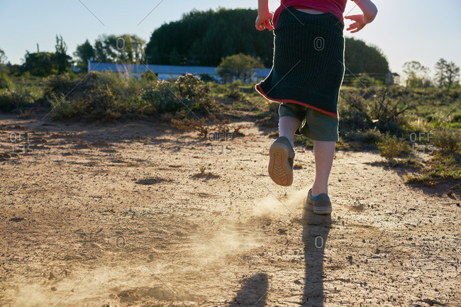 Boy kicking up dirt on a dirt patch in a scrubland