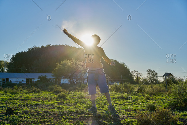 Boy standing in a grassy scrubland throwing dirt in the air