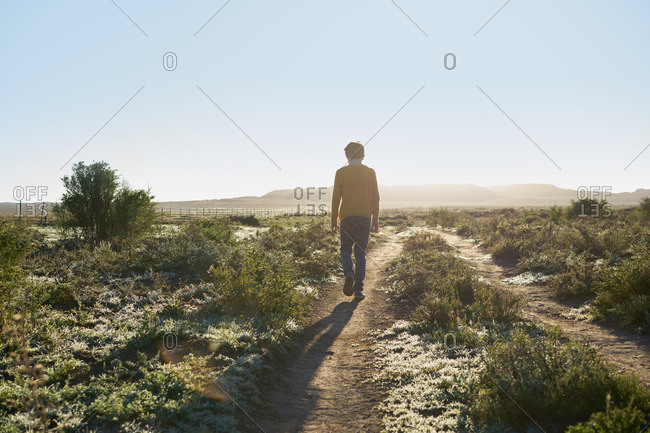 Boy walking on a rural dirt road in a desert scrubland