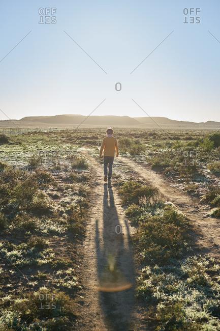 Boy walking in ruts on a rural path in a scrubland