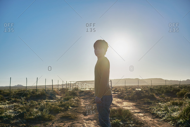 Boy standing on a rural dirt road in a scrubland