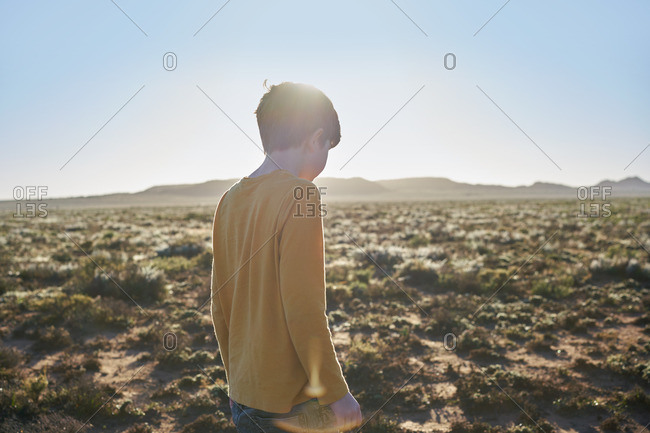 Boy exploring a vast desert scrubland