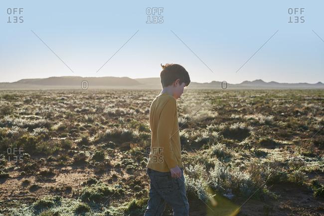 Boy walking between vegetation in a desert scrubland