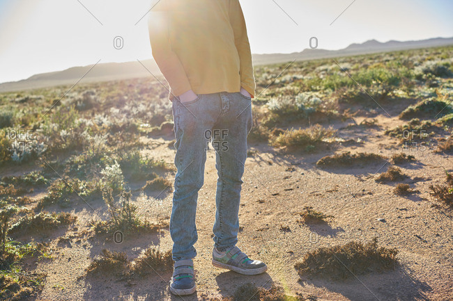 Legs and feet of a boy standing in desert scrubland