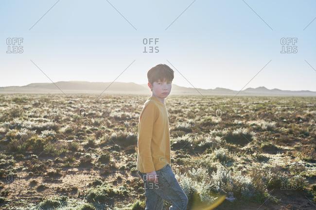Boy standing in a vast desert scrubland