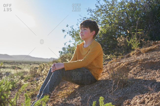 Boy sitting on a dirt hill looking at a desert scrubland
