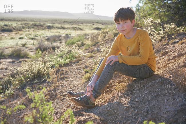 Boy sitting on a dirt hill in a desert scrubland