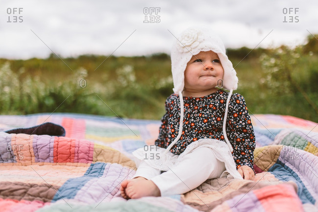 Portrait of a toddler sitting on a quilt in a meadow