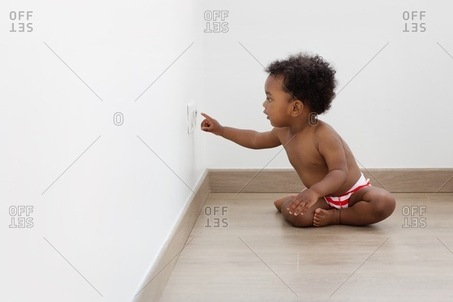 Child sitting on the floor pointing at an electrical outlet