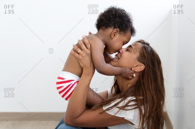 Mother sitting against a wall nuzzling her son