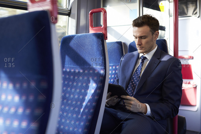 Businessman using digital tablet on train during commute