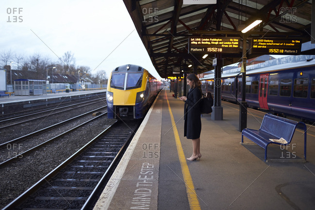 Oxford, United Kingdom - December 9, 2015: Businesswoman on platform waiting for train