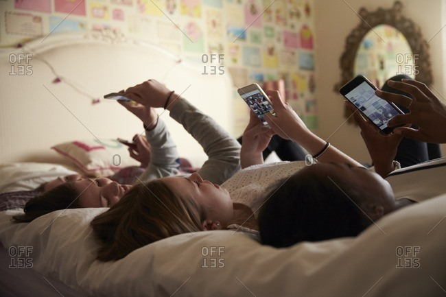 Teenage girls using cellphones in bedroom at home
