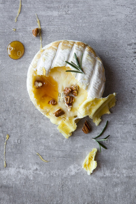 Overhead view of soft cheese drizzled with honey and nuts