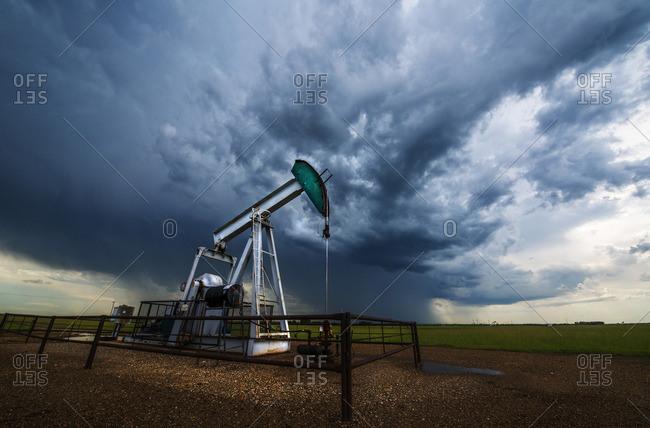 Pump jack, oil well, in field with stormy sky, Canadian prairies, Saskatchewan, Canada