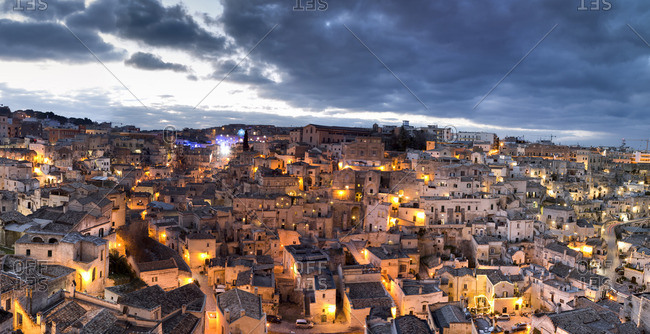 Houses of Sassi di Matera illuminated at dusk, one of the three oldest cities in the world, Matera, Basilicata, Italy