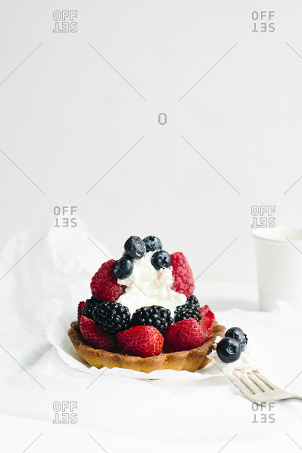 Fresh berry and cream tartlet with a bite missing
