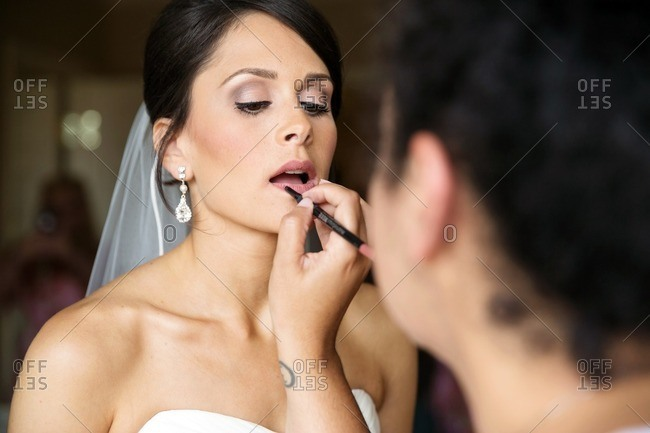 Woman putting lip liner on a bride