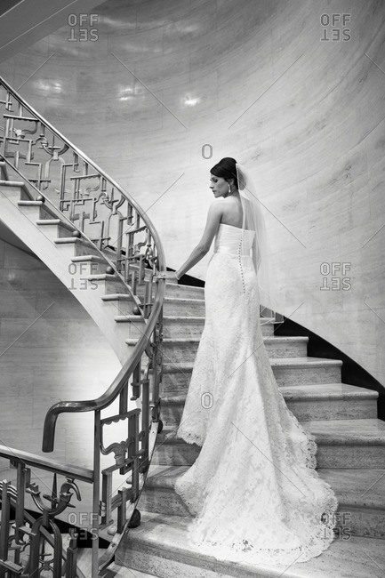 Bride walking up a spiral staircase