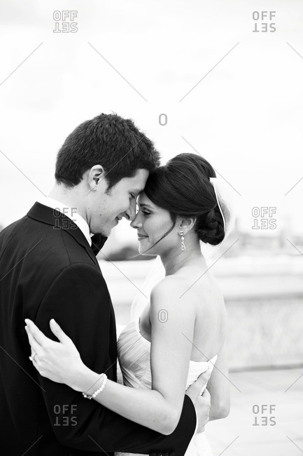 Bride and groom embraced on a rooftop