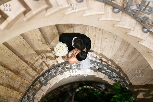 High angle view of bride and groom embraced on a spiral staircase