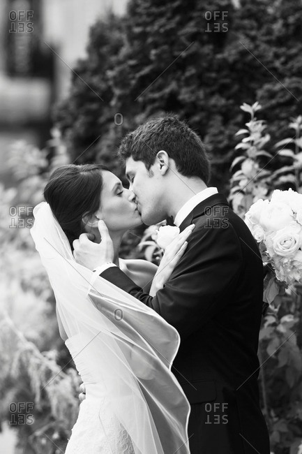 Happy bride and groom embraced in a kiss