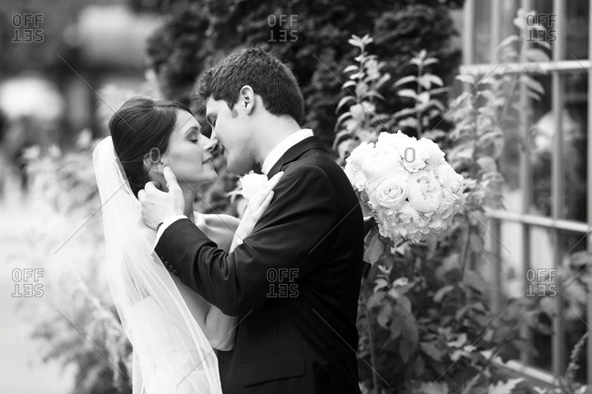 Happy bride and groom kissing outside