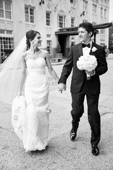 Happy bride and groom crossing a street while holding hands