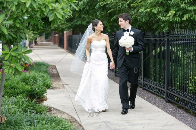 Happy bride and groom walking down a sidewalk holding hands