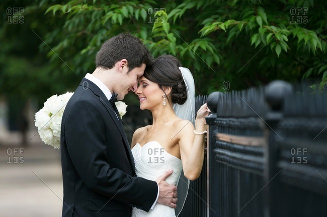 Bride and groom embraced by a wrought iron fence