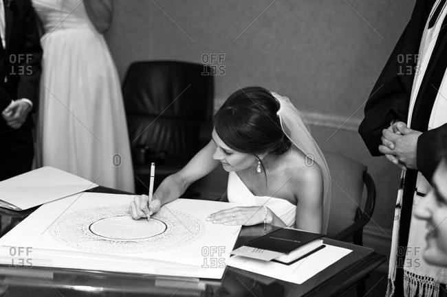 Bride signing a ketubah
