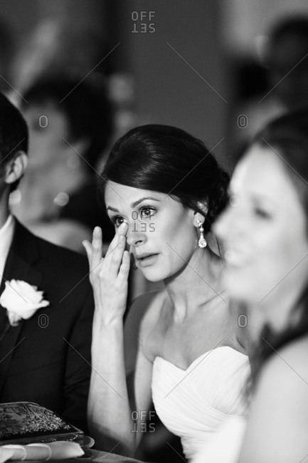 Bride wiping tear from her eye