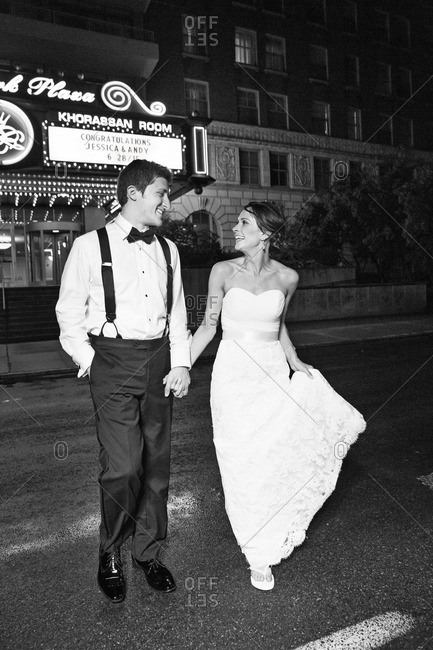 St. Louis, Missouri - June 28, 2015: Newlyweds crossing the street holding hands on their wedding night