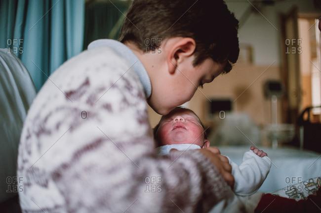 Boy kissing a newborn baby