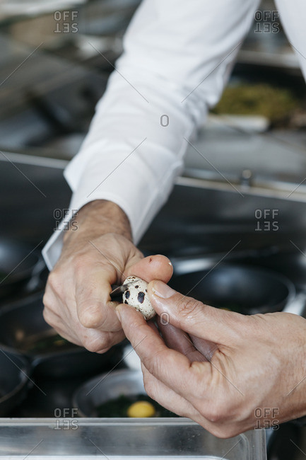 Chef cracking a small quail egg
