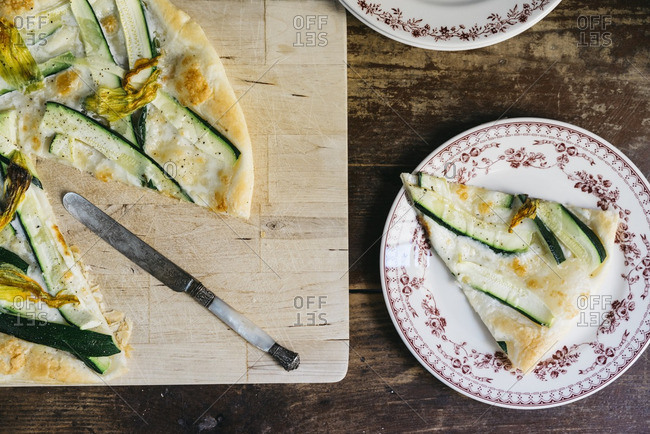 Slices of squash blossom, zucchini and mozzarella tart served on floral pattern porcelain plates
