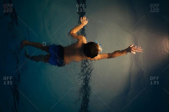 Boy swimming by pool light