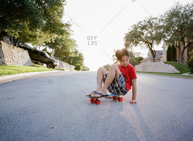 Boy sitting on skateboard in street