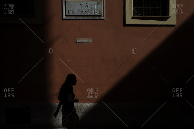 Silhouette of a woman walking past an orange building in Rome