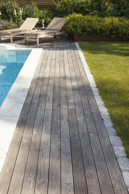 Wooden deck with lounge chairs beside a pool