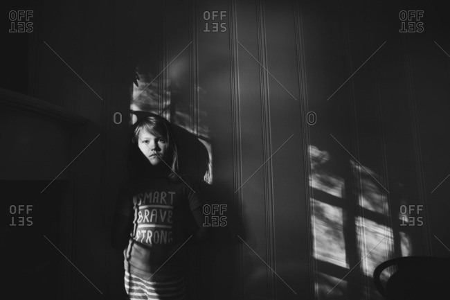 Black and white portrait of a young girl standing in shadow