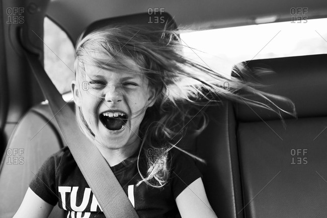 Young girl yelling from the backseat of a car