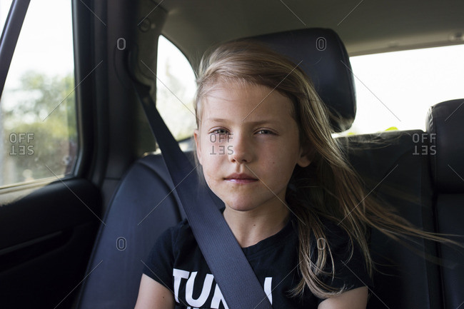 Young girl riding in the backseat of a car